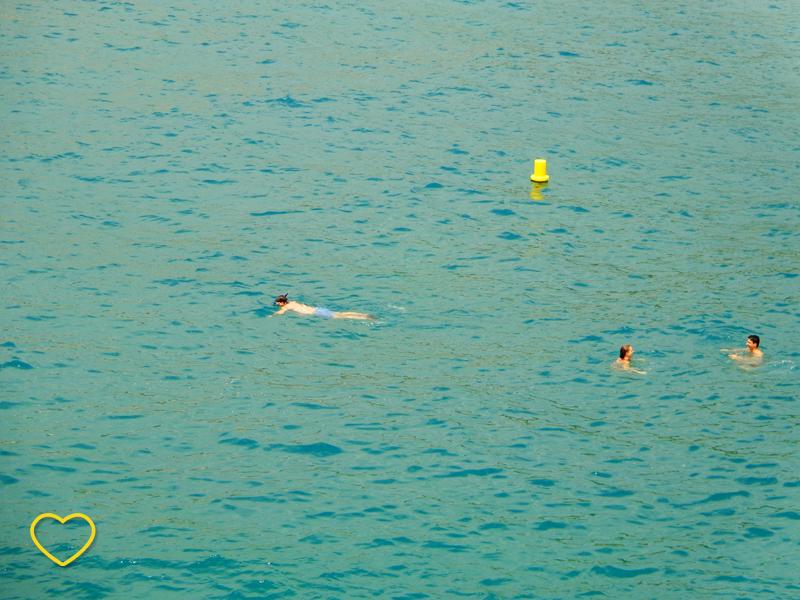 O mar azul turquesa e três pessoas nadando.