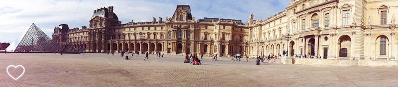 Panorâmica do pátio do Louvre, onde se vê a pirâmide e o edifício do museu.