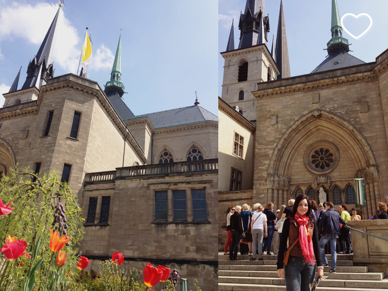 Duas fotos. Na primeira se vêem tulipas vermelhas e laranja de baixo para cima e uma parte da Igreja Notre Dame de Luxemburgo. Na segunda, está a mesma igreja, de outro ângulo, e eu na frente.
