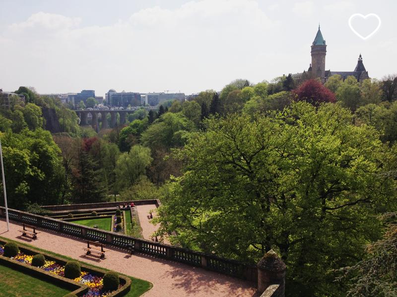 Um lindo parque urbano, muitas árvores, um aqueduto ao fundo e uma torre.