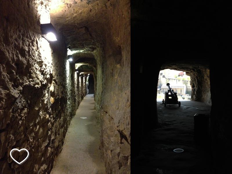 São duas fotos. Uma mostra um corredor que é uma das passagens, com paredes de rocha e alguns focos de luz. A outra mostra uma das câmaras do rochedo com um canhão apontado para uma espécie de janela.