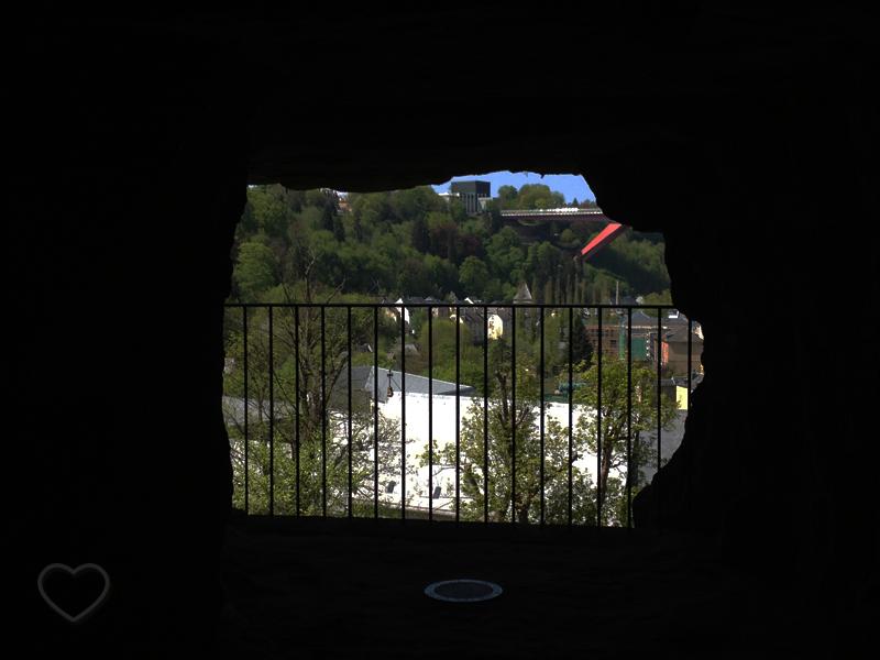 """Uma espécie de janela irregular, uma abertura no rochedo. A foto foi tirada de dentro de uma passagem no rochedo e se vê a cidade através da """"janela""""."""