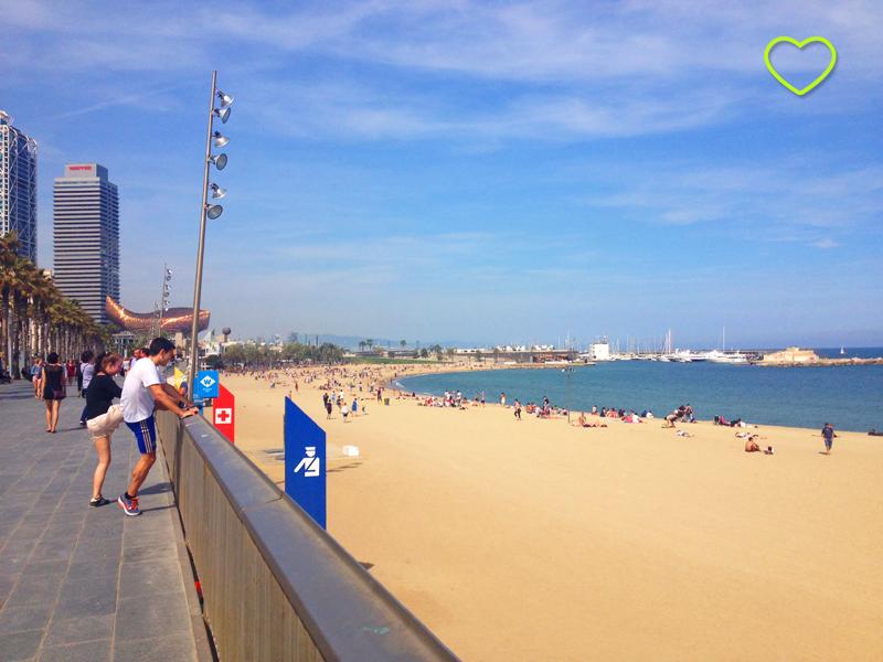 Foto de uma das praias de Barcelona. Tirada da calçada. Vê-se gente exercitando-se na calçada, um prédio que tem um formato que lembra uma baleia, a areia e o mar.