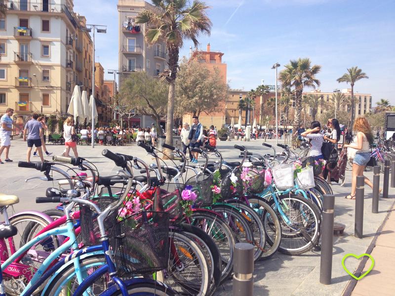 Orla da praia em Barceloneta. A praia não está no enquadramento. Vê-se uma fileira de bicicletas coloridas para aluguel.