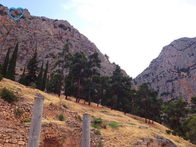De baixo para cima: duas colunas, uma colina, a vegetação de árvores e ciprestes e as montanhas.