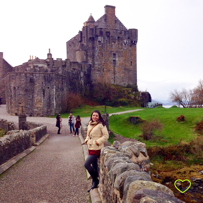 Eu na ponte que leva ao castelo. E o castelo ao fundo.