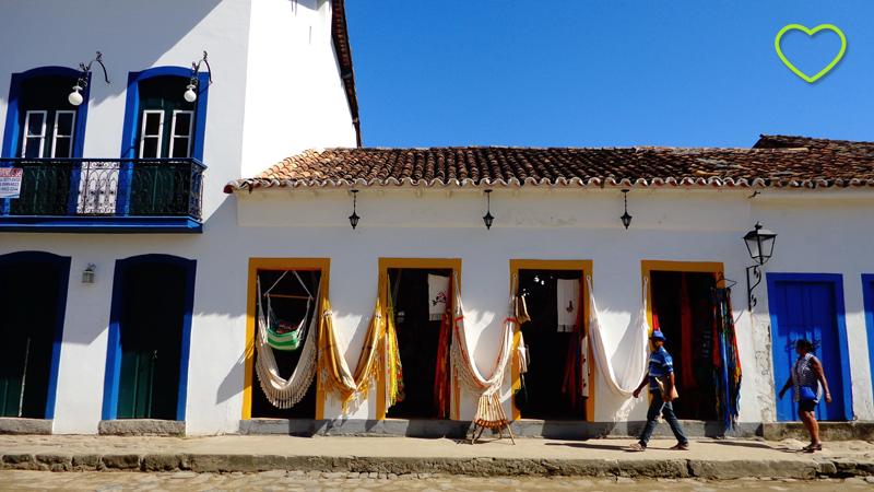 Fachada de arquitetura colonial e várias redes coloridas penduradas.