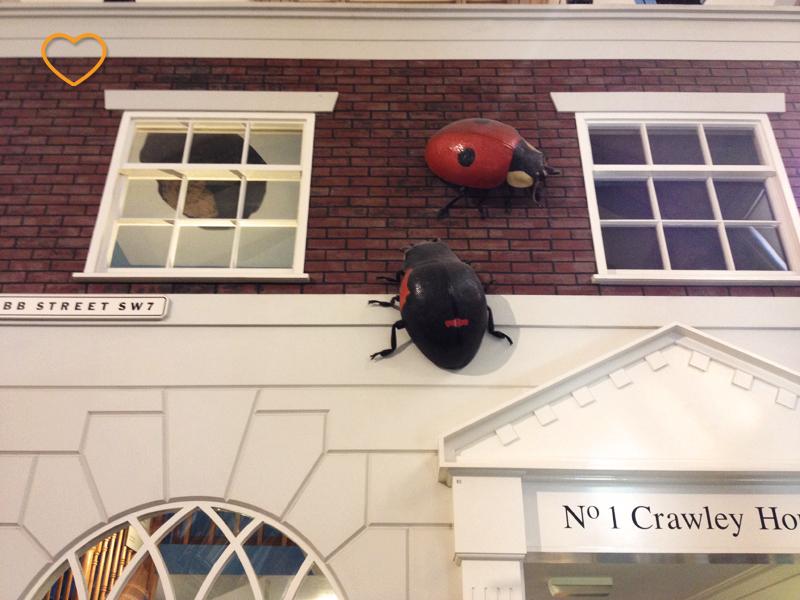 Uma fachada de casa cenográfica com uma joaninha é um besouro gigantes.