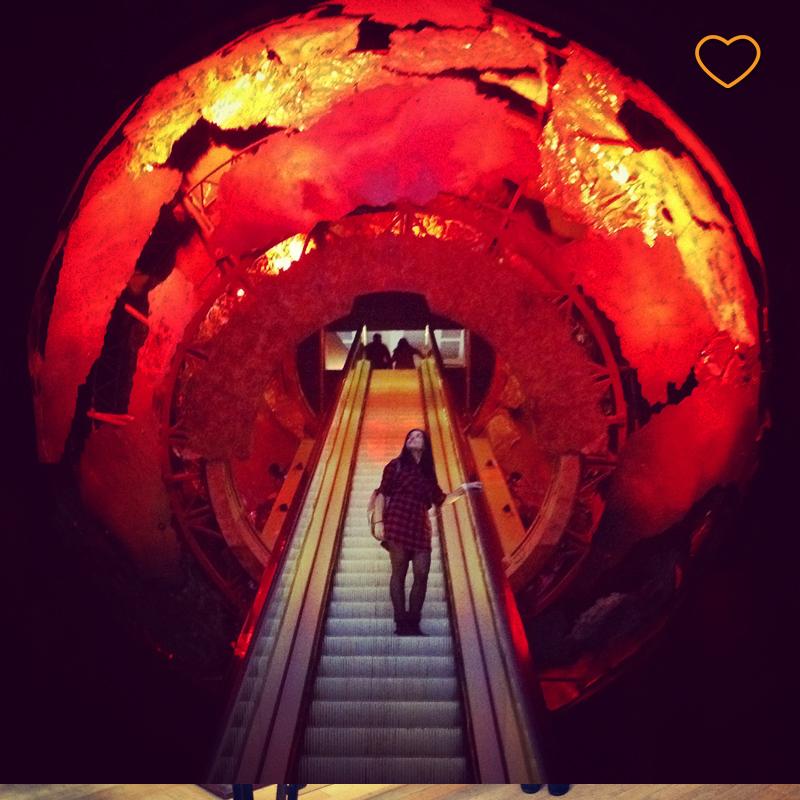 Eu subindo em uma escada rolante ao interior de um modelo de planeta Terra em formação.