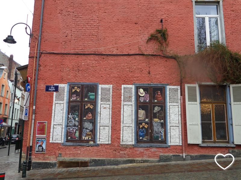 Garfitti em parede imitando janelas e prateleiras.