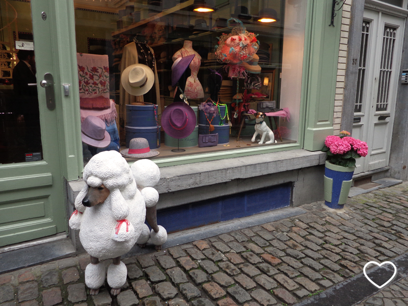 Vitrine com chapéus e, do lado de fora da loja, um boneco de poodle.
