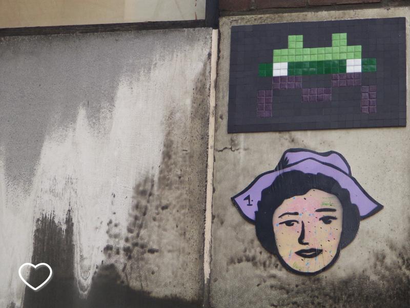 Grafitti em parede. Uma moça com um chapéu lilás.