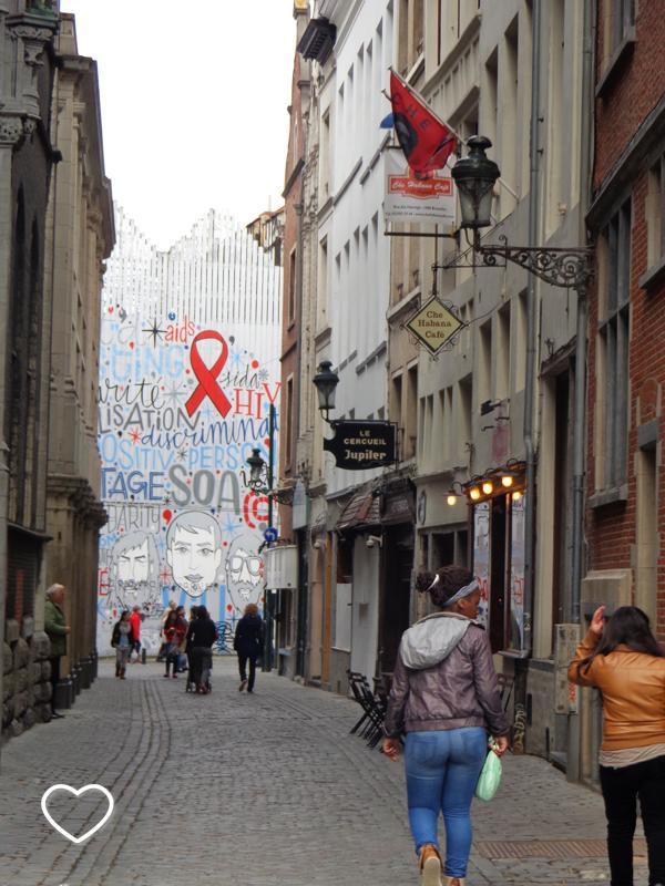 Garfitti em uma parede ao fundo de uma ruela. Mostra um símbolo de prevenção à aids.