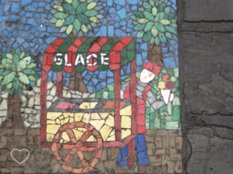 Mosaico que mostra uma barraquinha de sorvete na calçada.