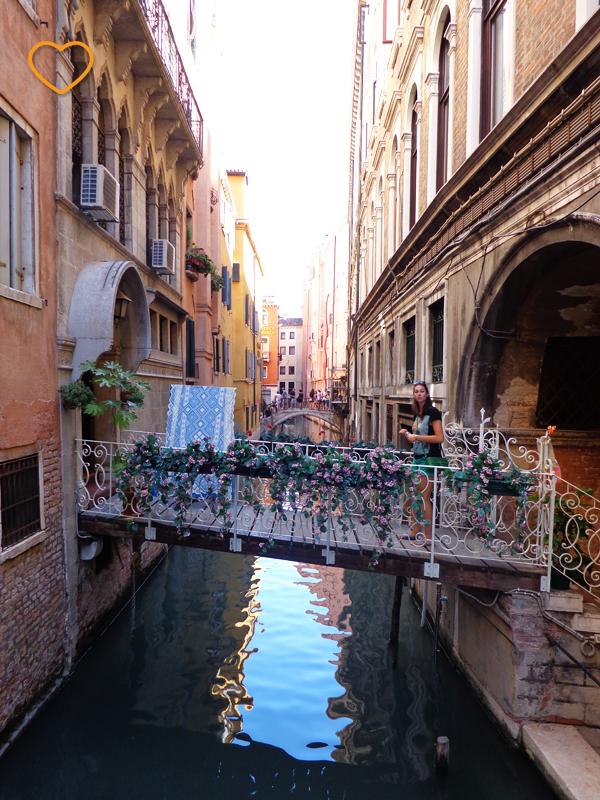 Uma ponte pequenina e enfeitada com flores liga um prédio a outro. E um canal embaixo.