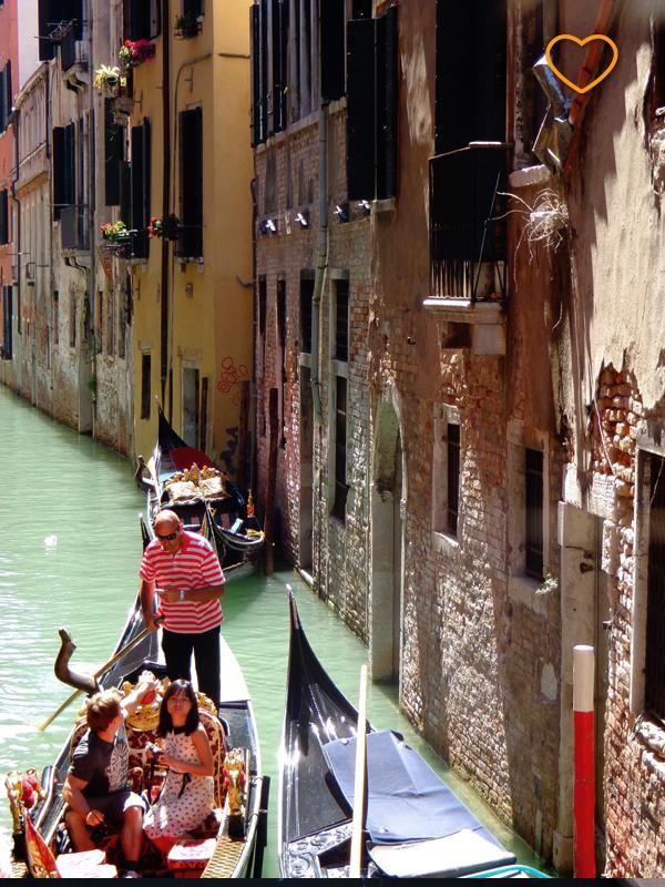 Em um canal estreito, um gondoleiro leva um casal para passear.