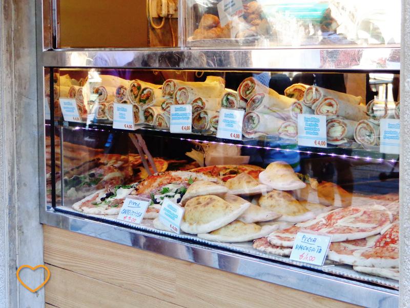 Uma vitrine cheia de comidas de massa.