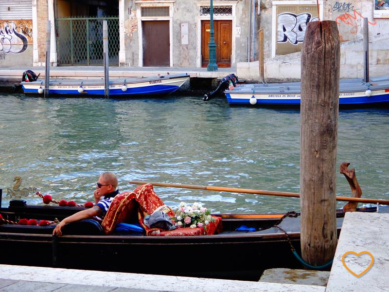 Um gondoleiro na sua gôndola falando ao celular. Há um buquê de flores na parte de trás da embarcação.