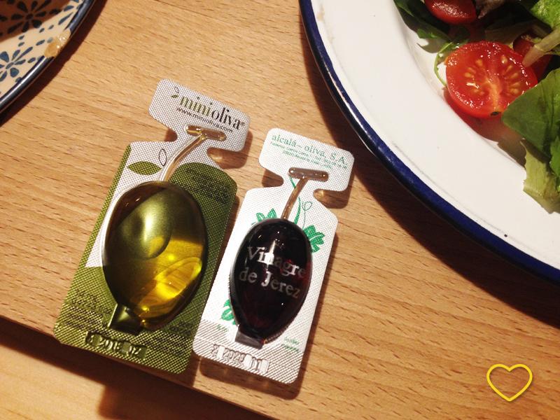 Embalagem de azeite de oliva e vinagre. A de azeite é em forma de azeitona e a de vinagre, de uva.