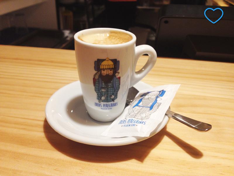 Xícara de café com o desenho do mascote do restaurante: um peregrino. Saquinho de açúcar também.