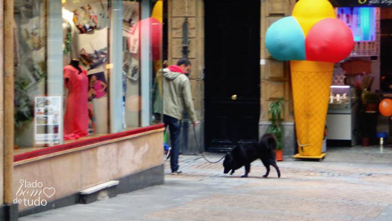 Numa esquina, um rapaz passeia com seu cachorro. Um sorvete enorme de decoração enfeita a porta de uma sorveteria.