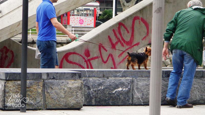 Numa mureta, um rapaz segura seu cachorro pela coleira. E um senhor se despede deles.