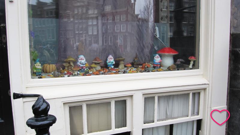 Janela de uma casa residencial, decorada com estatuetas de gnomos e cogumelos.