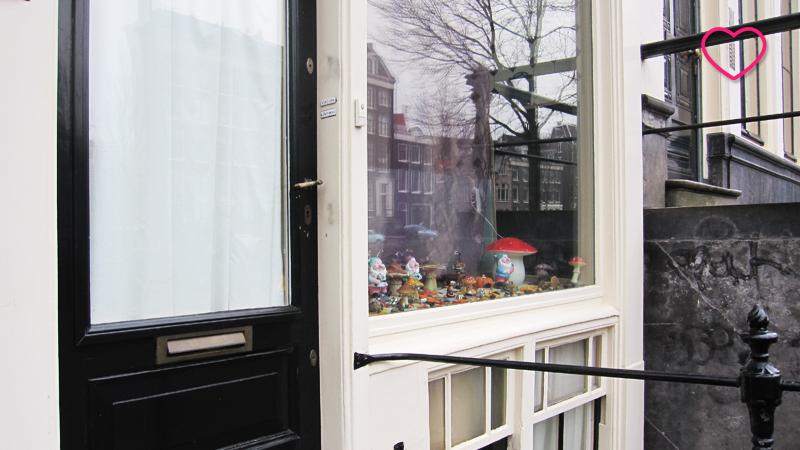Fachada de uma residência onde se vê a porta e a janela decorada com estatuetas de gnomos e cogumelos.