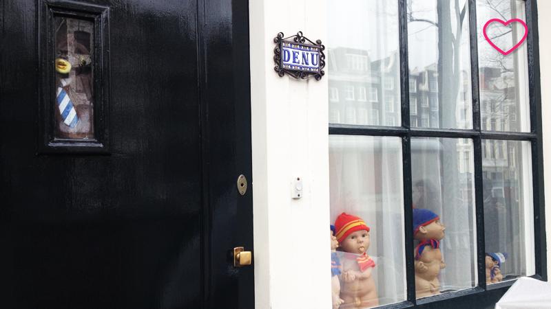 Uma fachada de um casa residencial onde se vê a porta e a janela decorados com bonecos.