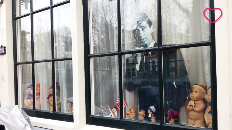 Foto de uma janela com o peitoril cheio de bonecos com caras de bebês. Também tem um recorte de fotografia de um homem em preto e branco.