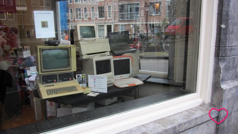 Janela de uma casa, desta vez um estabelecimento comercial, onde estão vários computadores antigos, como forma de decoração.
