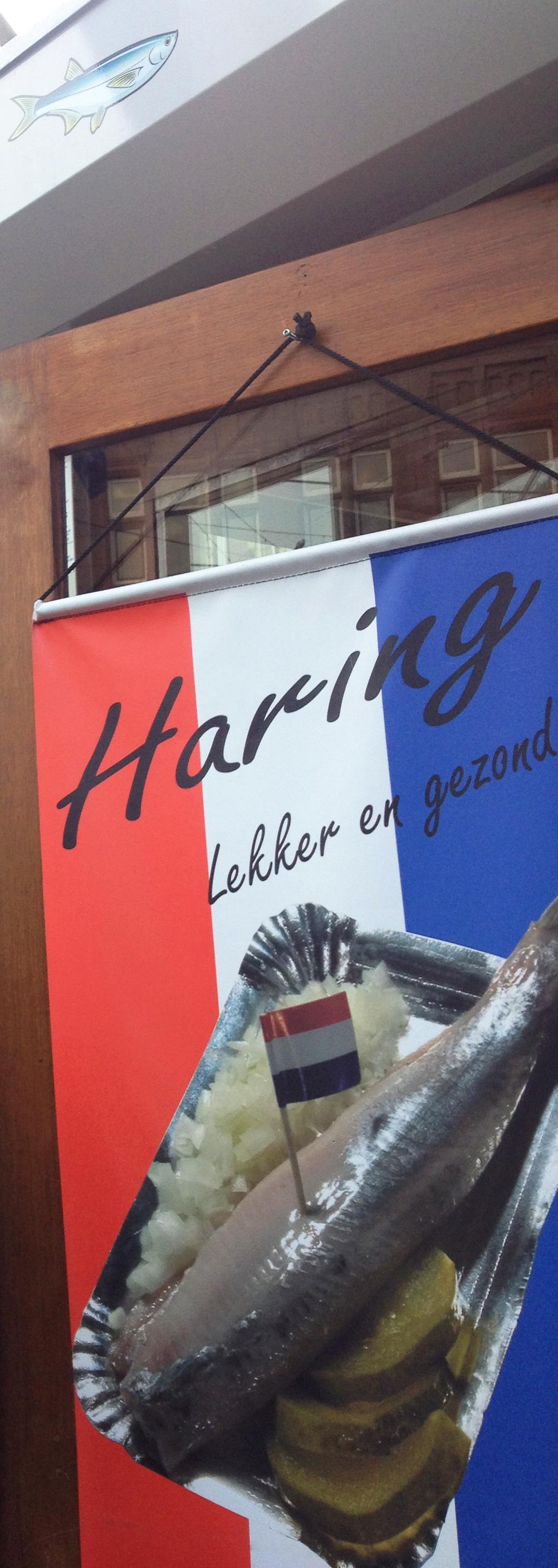 Foto mostra parte da barraquinha que vende haring, decorada com um banner que tem as cores da bandeira holandesa (vermelho, branco e azul) e uma imagem do haring.
