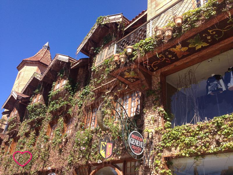 Detalhe de um edifício em estilo de montanha, com muitas plantas decorando sua fachada.