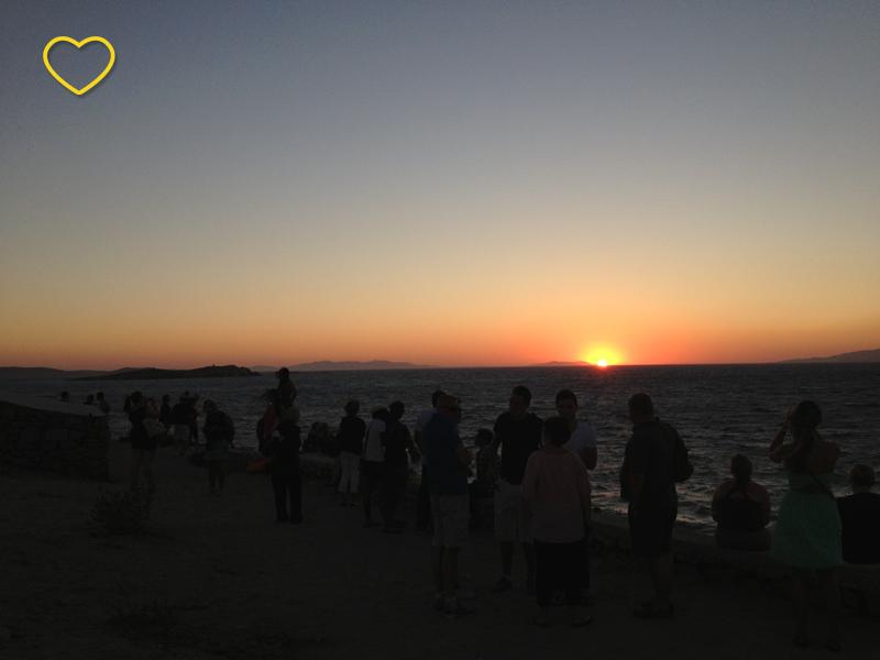 O pôr do sol e muitas pessoas assistindo.