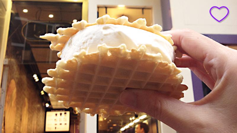 Em close, o sorvete, de cor branca, e no meio de dois biscoitos, tipo um sanduíche. Vê-se a minha mão segurando o sorvete. Ao fundo está a loja.
