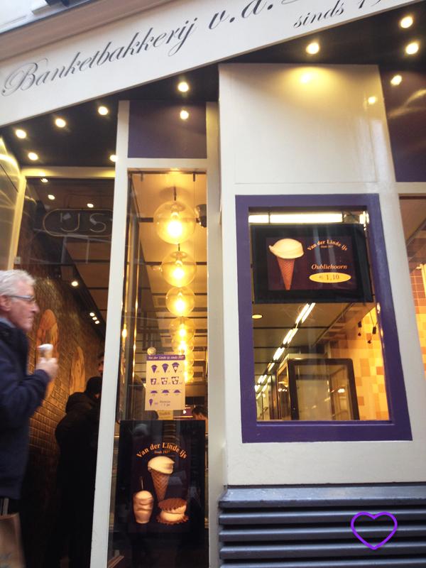 Fachada da Loja, pintada de branco e lilás. Tem um cartaz com ilustrações do sorvete e um esquema com as variações e os preços. O letreiro é com letra estilo manuscrita. Vê-se um senhor com um sorvete na mão, na porta.