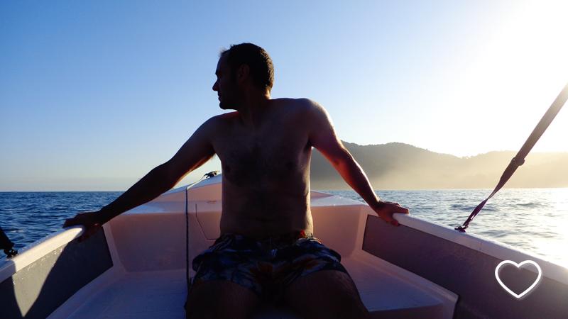 Silhueta de homem sentado na proa do barquinho. Ao fundo, a praia.