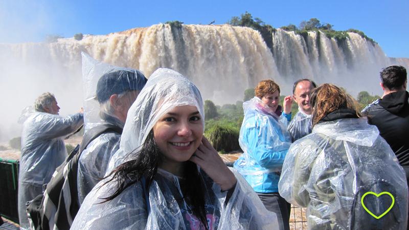 Eu, em primeiro plano, com capa de chuva e, ao fundo, as cataratas.
