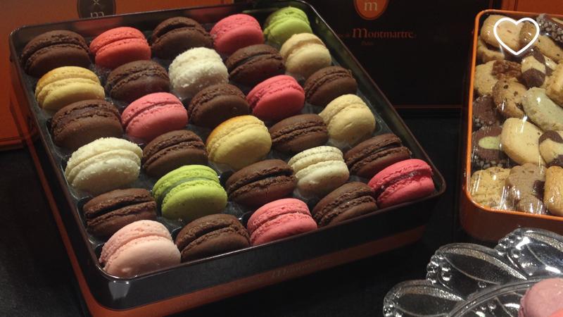 Vários macarons, de diversas cores, em uma caixa.