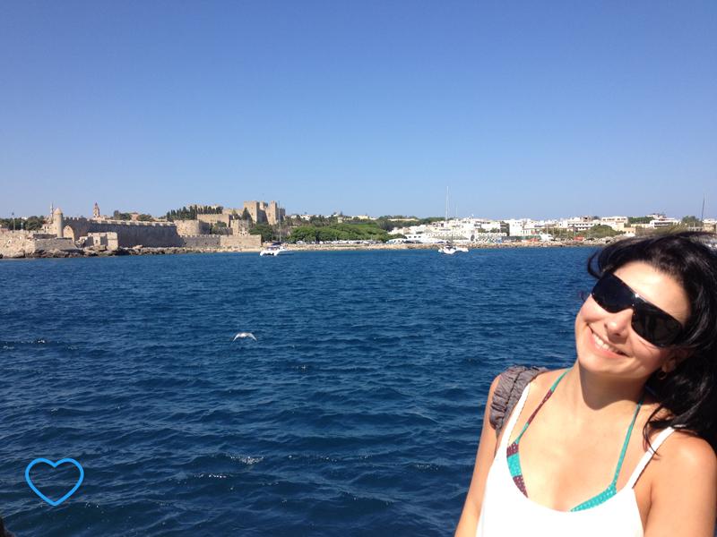 Eu, no porto de Rodes. Vê-se o mar bem azul, mais para o tom escuro. O céu azul claro e sem nuvens. A cidade amuralhada ao fundo.
