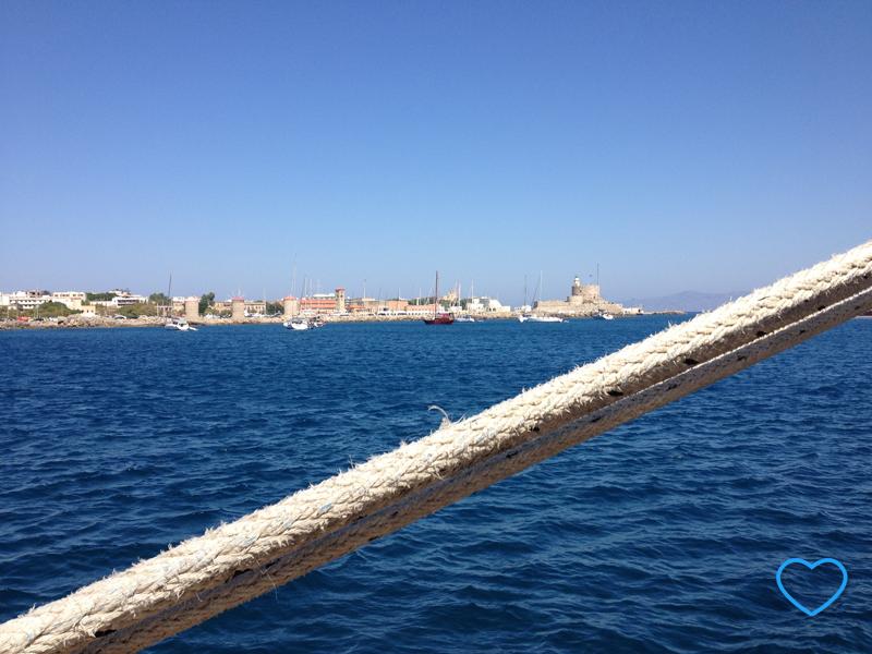 Uma corda, do porto, em primeiro plano. Em segundo plano, o mar azul escuro, e, ao fundo, a cidade amuralhada.