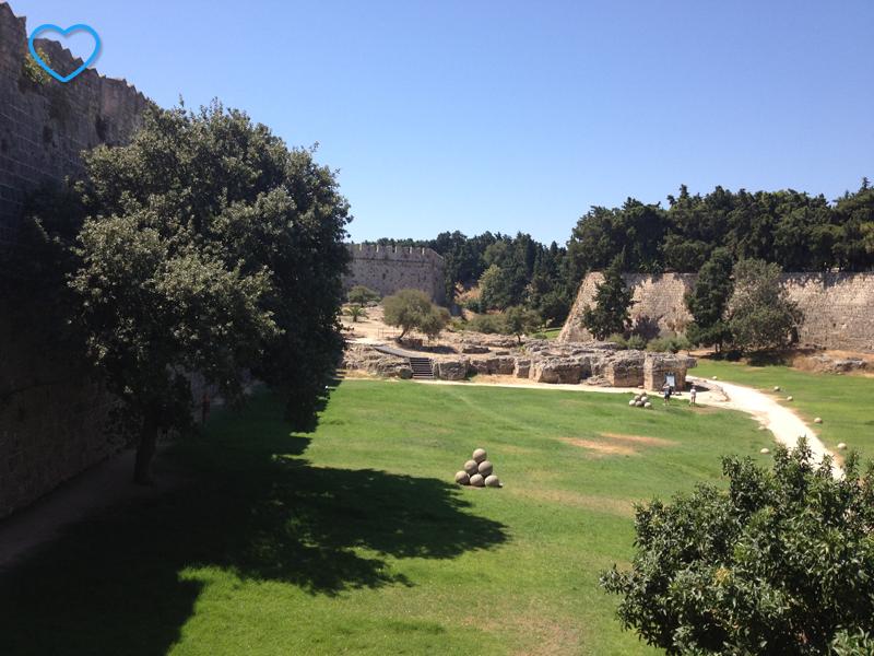 Um gramado com umas bolas de pedra. É o jardim do castelo.